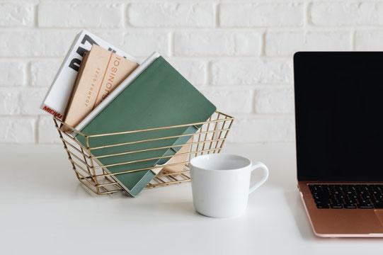 ゴールドに青いフォルムの腕時計をはめた腕。