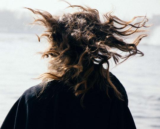 Rückenansicht von Frau mit wehenden Haaren am Wasser (Foto: Roman Drits, Barnimages)