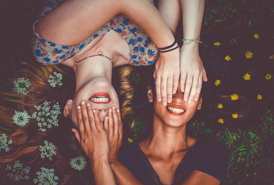 Zwei Frauen zeigen ihre Zähne