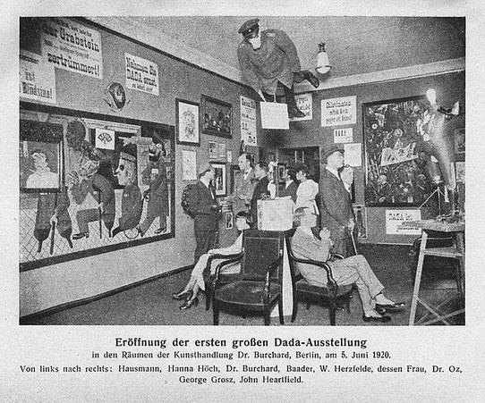 ダダ初個展のグランドオープニング:1920年6月5日、ベルリン国際ダダ展。天井から吊るされて中央の人物は、豚の頭を持つドイツ将校の彫像だった。左からラウル・ハウスマン、ハンナ・ヘッヒ、オットー・ブルヒャルト、ヨハンズ・バーダー、ヴィーラント・ヘルツフェルデ、マルゲレート・ヘルツフェルト、Dr.Oz、ジョージ・グロス、ジョン・ハートフィールド。