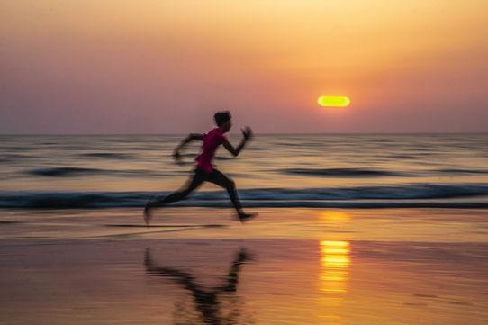 Ein Mann in Sportkleidung rennt am Strand bei Sonnenuntergang im Hintergrund.