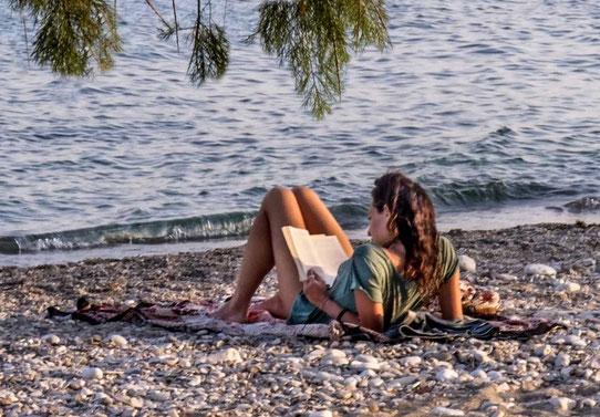 femme-sur-la-plage-allonge-en-train-de-lire-un-livre-seule-face-a-la-mer