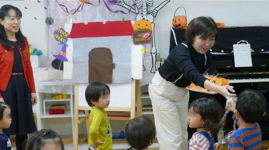 幼児教室でハロウィンにちなんだリトミックを行い、最後にお菓子を生徒に渡しました。