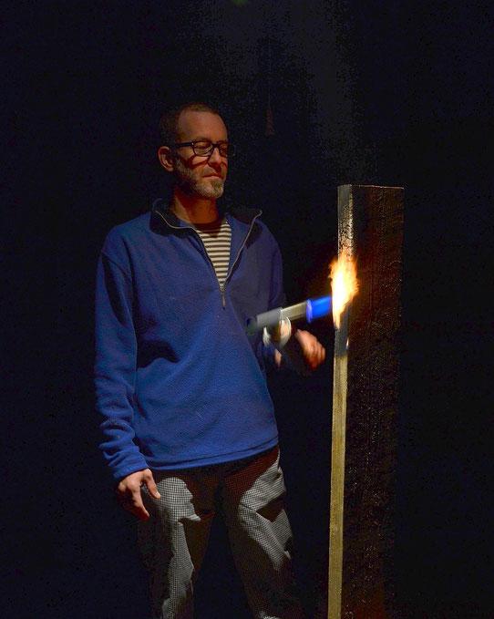 Der Künstler Holger Schulz Schweden, beim Flämmen von Holz