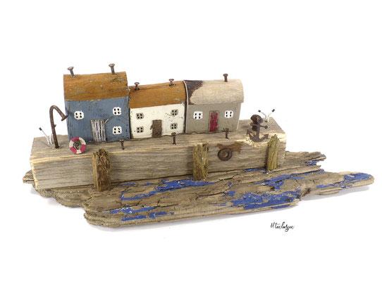 Treibholzdeko mit Fischerhäusern im Hafen