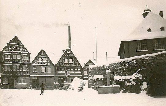 Der verschneite König-Adolf Platz. Im Hintergrund raucht der Schornstein der Fabrik Landauer auf dem heutigen Löherplatz.