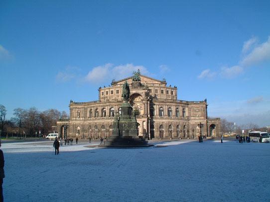 Een blik op de Sächsische Staatsoper op de Theaterplatz met op de voorgrond een beeld van de Saksische koning Johann.