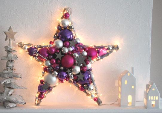 Großer Stern aus Glaskugeln in den pink, violett, silber und weiß, mit Beleuchtung - auf Kamin mit weißen Treibholzbäumen und Teelichtern dekoriert.