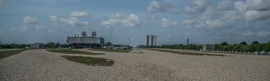 Le gros engin sur la gauche permet de transporter les fusées du Hangar qu'on voit au loin au milieu. Le gravier, c'est la route que prend l'immense engin !