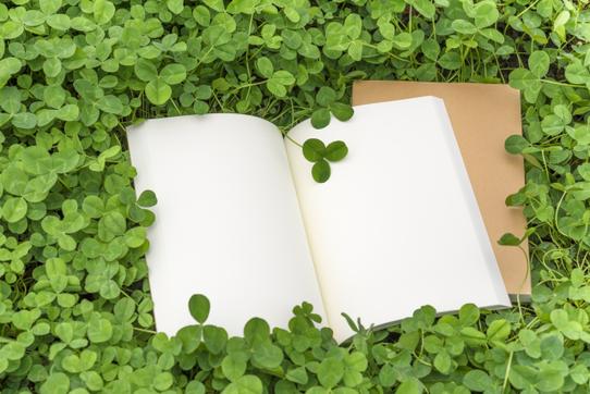 オフィスの打ち合わせテーブルでノートパソコンの画面を頬杖をついてチェックするビジネスウーマン。紺のジャケット姿。