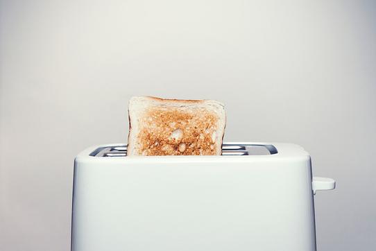 コーヒーの入った白のカップ&ソーサ。パソコンのマウス。白の電卓。ピンクのチューリップ。