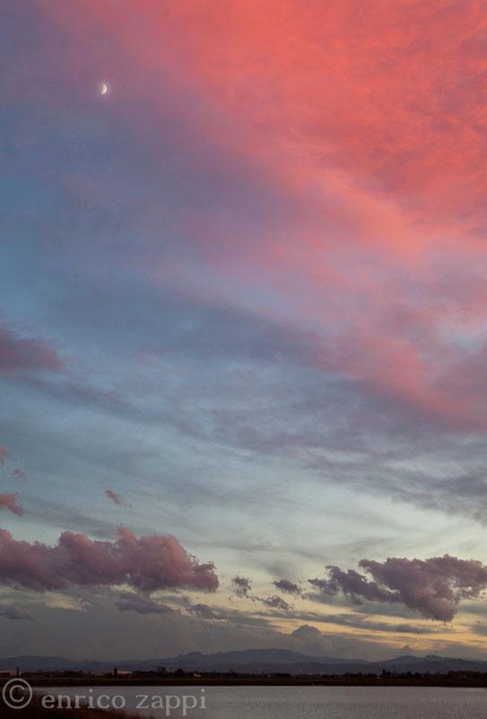 Tramonto alle Saline di Cervia: anche la minuscola luna contribuisce a dare un tocco di fascino ai colori accattivanti.