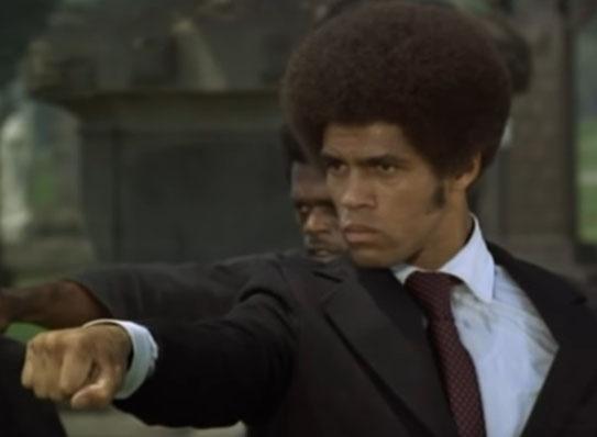 Auf dem Bild ist Jim Kelly in einem schwarzen Herrenanzug zu sehen. Man sieht nur den Oberkörper. Er führt einen Karateschlag aus.
