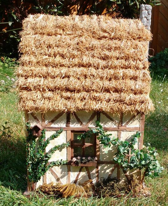Miniaturhaus mit Strohdach
