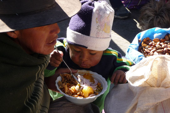 """Het straatbeeld op een lokale markt. De kinderen eten mee bij moeder op straat . Het contrast met """"onze wereld"""" is dan ineens weer erg groot."""