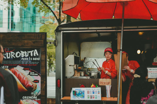 an asian girl selling japanese hotdogs at a food truck