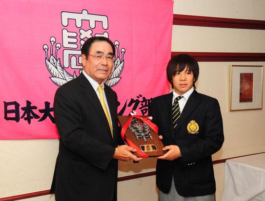 送別会では今年度の表彰式も行われ、高橋財務担当(S43)から優秀選手賞を授与される村田夏南子選手(文理体育2年)