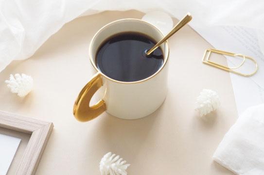 オフィスのデスクで資料を広げてノートパソコンのキーボードに打ち込む女性の指先。コーヒーの入ったカップ&ソーサ。新聞。メモ帳と鉛筆。眼鏡。