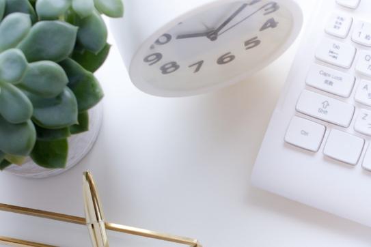 パソコンのキーボードの横に置かれた白の置時計と観葉植物の鉢植え。レターケースに立てかけられたゴールドのボールペン。