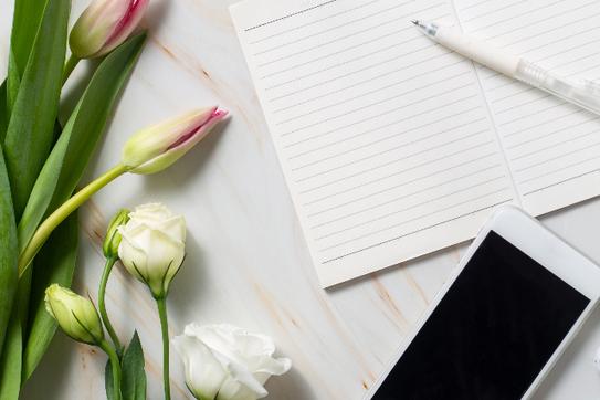 広げられたノートと白のボールペン。スマートフォン。ピンクのチューリップと白のバラの花。