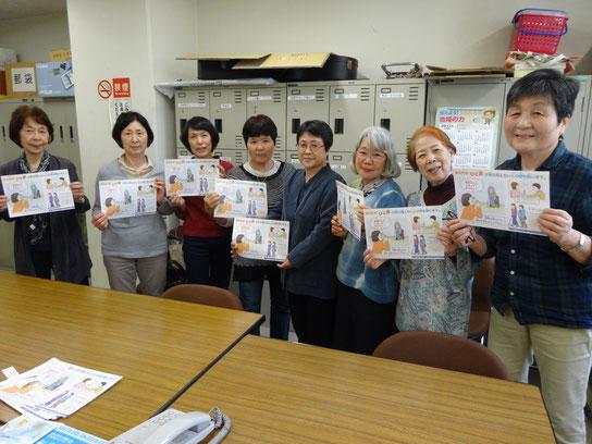 音訳活動の部屋で、「とも」のメンバー8人が、当会作成のチラシを持って、にっこり微笑んでいます。
