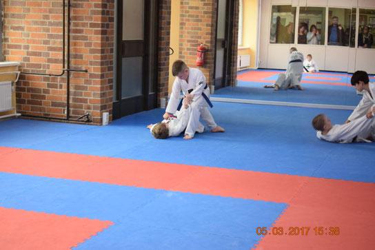 Selbstverteigungsübungen in der Taekwondo-Kindergruppe. Zwei Jungs trainieren die Selbstverteidigung. Ein Junge liegt am Boden und der zweit Junge hält ihn fest.