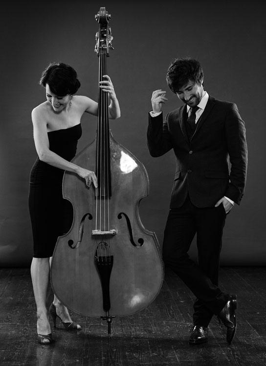 Musikerin spielt Cello und ein Musiker steht neben ihr und schnippt mit den Fingern