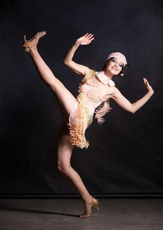 Tänzerin Ksenia Parkhatskaya hebt das Bein in einem Charleston Kostüm