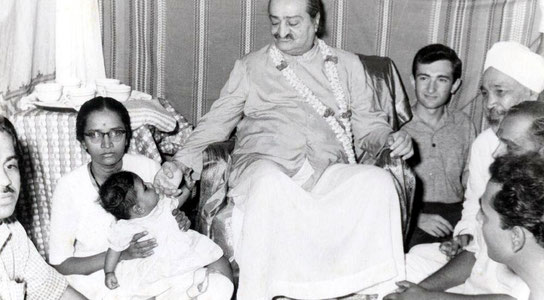 Meher Baba playing with a baby. Irwin Luck is seated behind Baba.