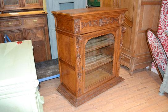 auf dem Foto sieht man einen antiken Vitrinenschrank aus Holz mit vielen schönen Schnitzereien, den man bei Nouvelle-Antique aus Aachen kaufen kann.