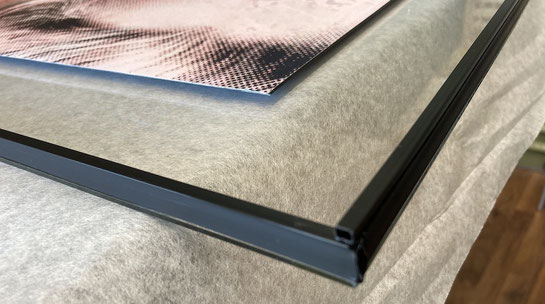 Glassandwich mit schwarzen Distanzleisten auf Bilderglas fixiert.