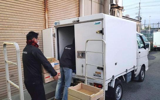 軽貨物トラックに荷物を積み込む作業