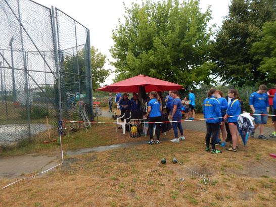Beim Hammerwerfen drängten sich viele unter den schützenden Schirm.