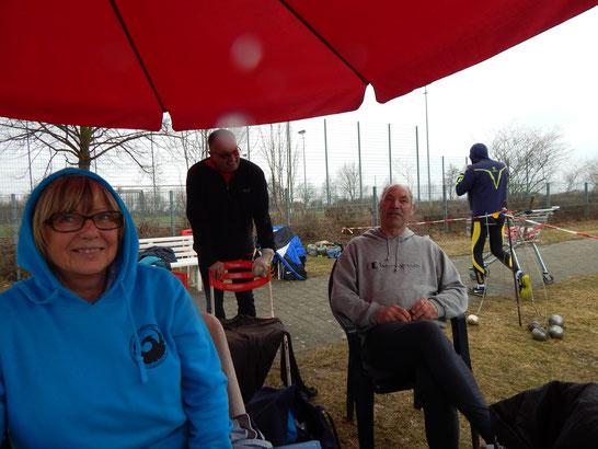 Im Schutze des Schirms tummeln sich Gertrud Böhm, Roland Klingler und Helmut Hessert (v. l. n. r.), derweil Dr. Klaus Lutter (im Hintergrund) das Weite sucht.
