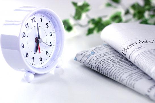 英字新聞2紙と白の置時計。