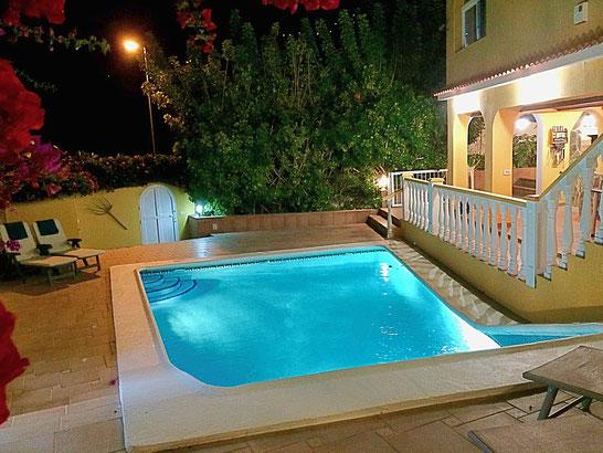 Beleuchteter Pool bei Nacht.