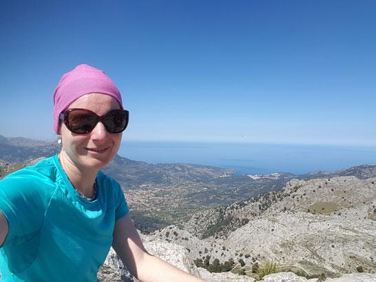 Auf dem Bild ist Sandra Lehner auf dem Gipfel eines Berges zu sehen. Im Hintergrund ist das Meer zu sehen.