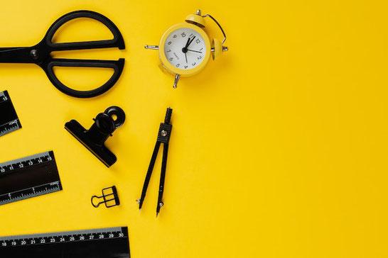 オフィスのデスク。張り紙が壁に貼られている。