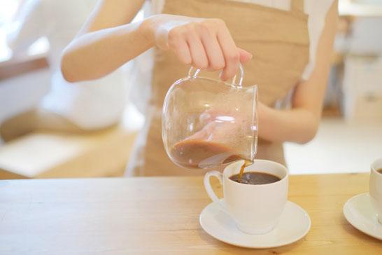 カフェでコーヒーを淹れるパート店員。ベージュのエプロン姿。