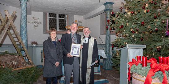 Kirchenvorsteherin Simone Möller und Volker Weinmann (rechts) ehrten Helmut Rommel für 50 Jahre an der Orgel | Foto→ Heiko Weiß