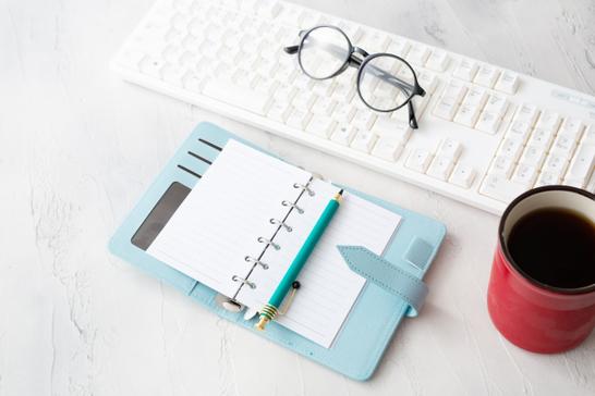 観葉植物のあるオフィスのオープンスペースのテーブルでノートパソコンを広げるビジネスウーマン。コーヒーを飲みながら。