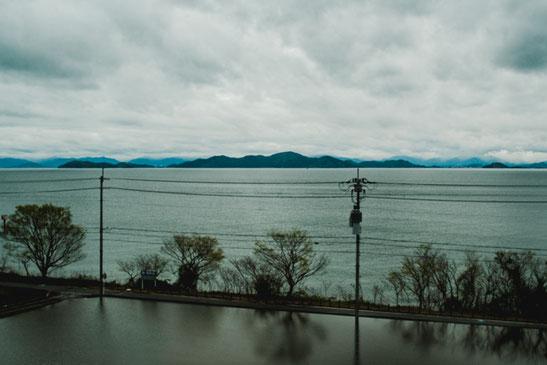 湖西線に沿う琵琶湖沿岸に水田。対岸の山は意外に近く感じられます。