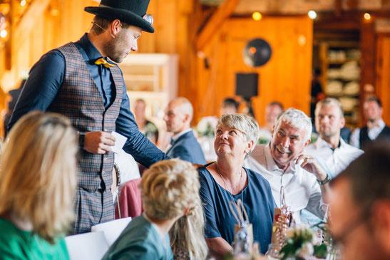 Magier Johannes verzaubert gespannte Gäste an einem runden Tisch in einem großen Saal