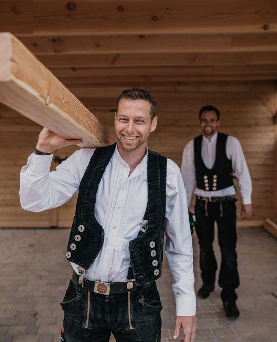 Lächelnde Zimmerer unter einem Carport aus Holz