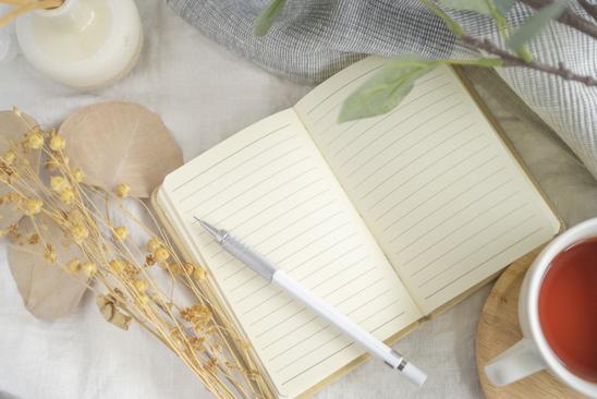 電卓を手に持ったビジネススーツ姿の女性。