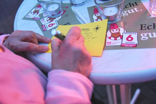 Eine Passantin schreibt ihre gute Tat auf eine Karte © Theresa Meier