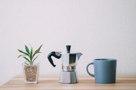 テーブルに置かれたコーヒーミルとマグカップ。卓上サイズの観葉植物。