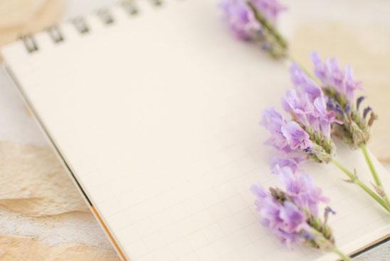 パソコンのキーボードの上に置かれた眼鏡。付箋の貼られたメモ帳、ボールペン、タブレット、観葉植物のグリーン。