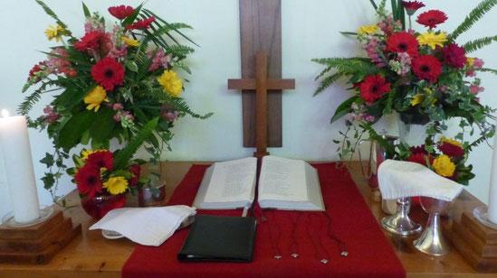 Bild unseres Altar mit Kreuz, Bibel, Kerzen, Blumen und Abendmahlsgeschirr.