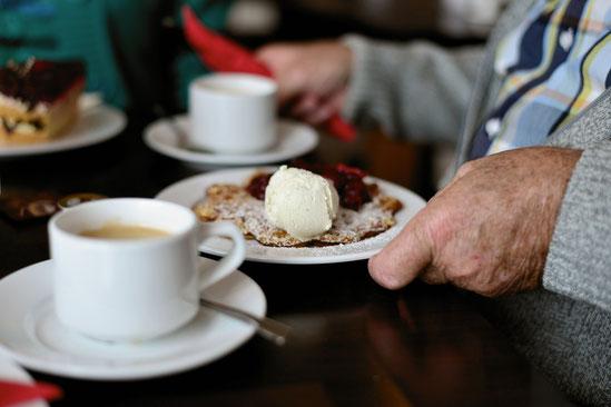 Symbolbild einer gedeckten Kaffeetafel: Auf einem Telle ist eine leckere Waffel mit einer Kugel Eis.